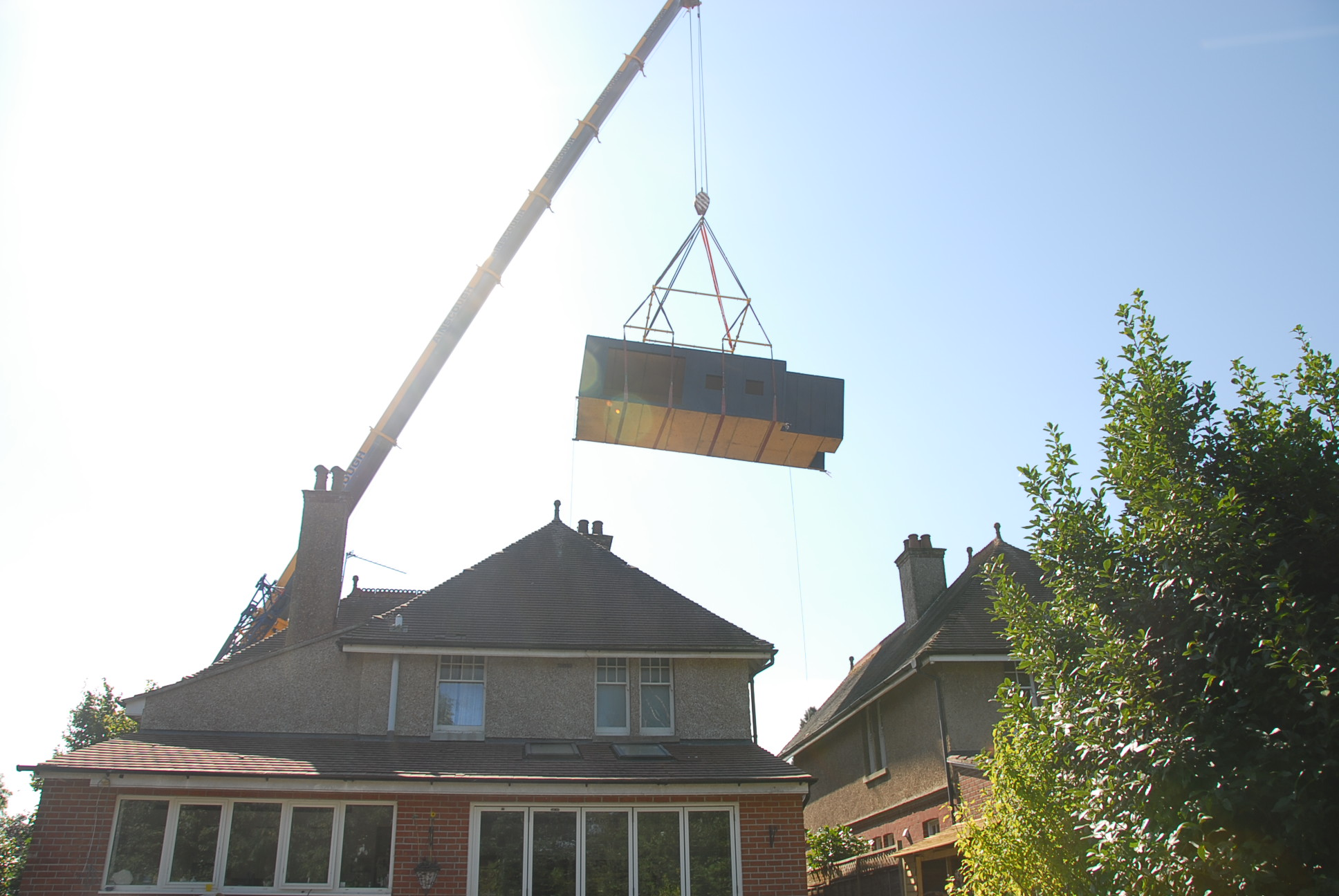 Modulift one-over-two-over-four spreader beam configuration lifting a modular building over a house